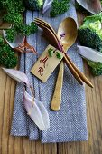 Wooden cutlery with a name label on a napkin between shallots and broccoli