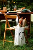 Bag of baguettes hanging on chair back in front of set table in garden