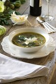 A bowl of minestrone soup made from green vegetables and pesto