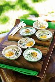 Baked eggs in oven-proof dishes with mushrooms, ham and herbs
