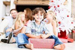 Boy sitting with wrapped Christmas gift