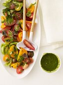 Tomato Salad with Pesto; On a Serving Dish with Salad Servers