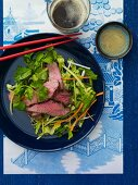 Asian Beef Salad on a Blue Plate with Chopsticks; From Above