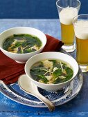 Two Bowls of Soup with Greens and Two Glasses of Beer