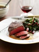 Partially Sliced Steak Cooked Rare with Beet Greens