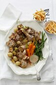 Chicken fricassee in a white wine sauce with vegetables and chips
