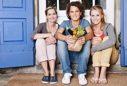 Two young women and a young man sitting in front of a door with vegetables