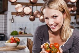 A young woman holding tomatoes winking at the camera