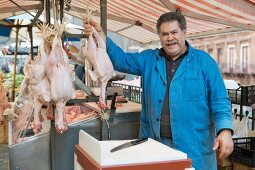 butcher on market presenting his goods