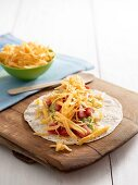Tortilla with tomatoes, guacamole and cheddar cheese
