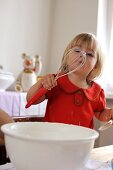 Young girl playing with whisk