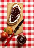 A slice of rustic bread topped with cream cheese and plum jam