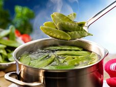 Mange tout being added to a pot of boiling water