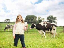 Mädchen mit einem Milchglas auf Kuhweide