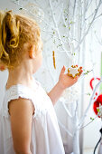 Little girl looking at Christmas biscuits hanging on tree