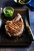 Grilled Rib-Eye Steak on a Dish with a Knife and Herb Sauce