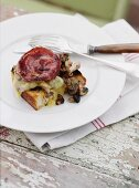 Toasted bread with mushrooms, cheese and bacon on a rustic table