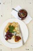 A plate of cheese with crackers, grapes and tsamma melon jam (South Africa)