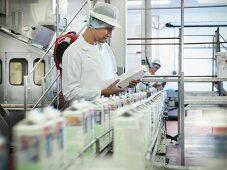 Worker inspecting goat's milk in dairy