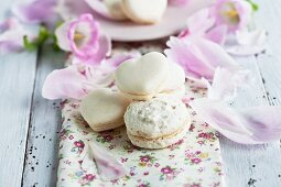 Vanilla macaroons with a rough surface; to the rear, heart-shaped macaroons