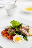 Quail's egg with tomato wedges, sliced potatoes and grilled tuna stripes