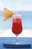 A cocktail on the beach, decorated with a flower