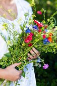 A woman holding a bunch of wild flowers in her arms