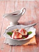 White quark dumplings with elderberry sauce and mint leaves