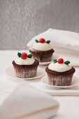 Icing sugar being sprinkled onto three wintry cupcakes
