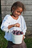 A girl with freshly picked damsons