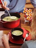 A man serving cauliflower soup
