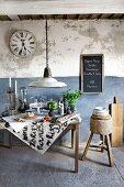 Vintage-Tisch mit Lebensmitteln und Küchenutensilien unter Glasglocken; dahinter eine rustikale Wand in Weiß und Blau