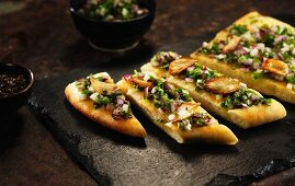 Unleavened bread topped with garlic, onions and herbs