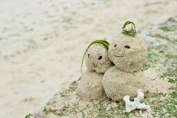 Man and woman figures made of sand on beach