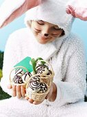 A girl, dressed as the Easter bunny, holding little baskets of chocolate eggs