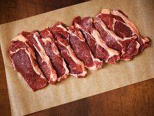 Raw Grass Fed Rib-Eye Steaks on Parchment Paper