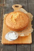 A whole lemon cake and a small sieve with icing sugar