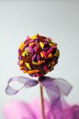 A cake pop decorated with dinosaur sprinkles