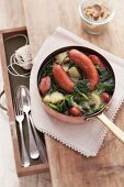 Green cabbage stew with pinkel sausage in a saucepan, seen from above