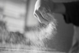 A backer sprinkling flour