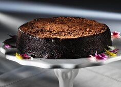 A chocolate truffle cake on a cake stand