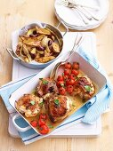 Chicken legs with feta and cherry tomatoes and a side of potatoes with onions and olives