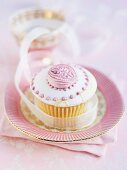 A cupcake with icing and pink decorations