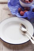 A fork and a spoon on a white plate with damsons in the background