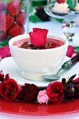 Strawberry soup with garnished with a red rose and a wreath of flowers decorating the plate