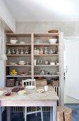 Rustikaler Esstisch mit Küchenstuhl und Baumstammhocker vor offenem Geschirrregal