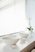 Verschiedene, handgearbeitete Schalen aus weißem Ton und Orchideentopf im weichen Licht einer halbgeöffneten Jalousie