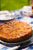 Whole Peach Upside Down Cake on a Sunny Outdoor Table
