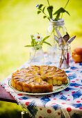 Peach Upside Down Cake with a Slice Removed; On a Table Outside
