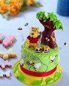 A child's cake decorated with a payout, bees and honey pots